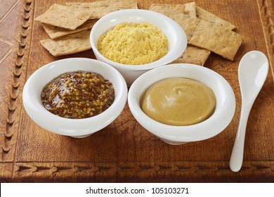 Three little pots with mustards in them - wholegrain, Dijon and hot English mustard powder, on an old wooden board.