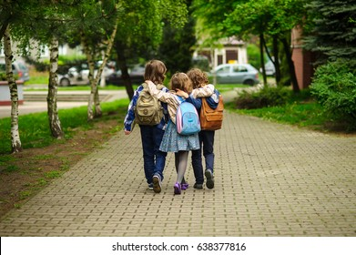 Three little school students, two boys and the girl, go in an embrace to school. Children's friendship. Serene spring day. View from a back.