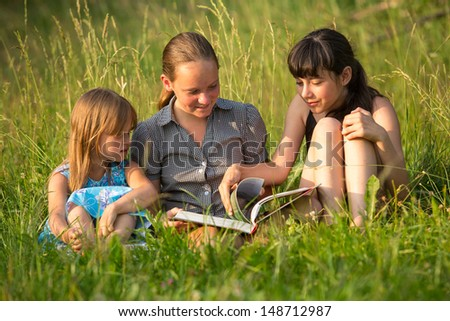 Three little sister reading book in natural environment together.