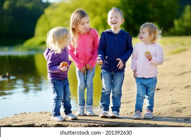 Three little sisters and their brother eating buns, laughing and joking by a river at sunny autumn day