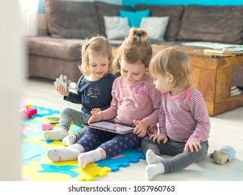 Three little sisters use tablet at home and sit in the middle of toys. Watching something funny.