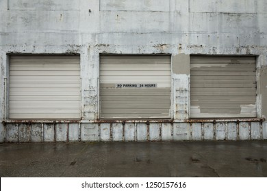 Three loading dock garage doors on an old warehouse, with painted over graffiti
