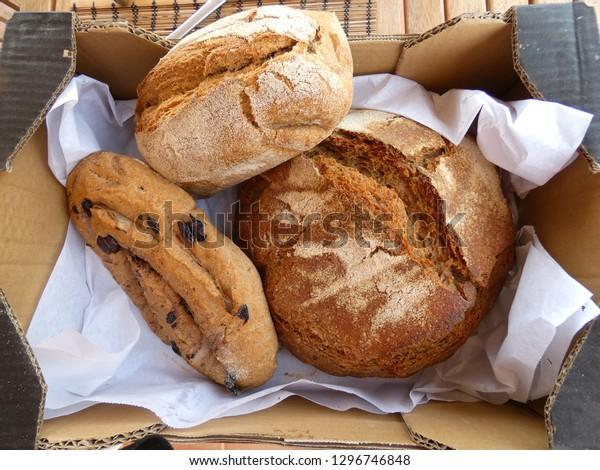 Three loaves of artisanal bread in a cardboard box from Spain