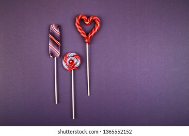 Three lollypops, striped lollypop looks like an ice-cream, round swirled and hart shaped  on a stick on violet background. Flat lay style.