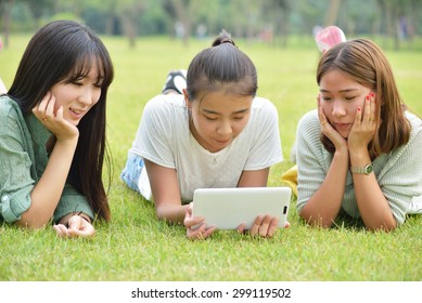 Three lovely girls lie prone on the grass.Use the tablet