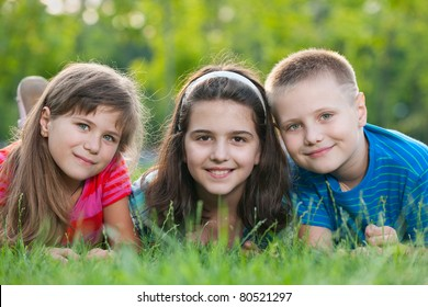 Three lying on the grass smiling children