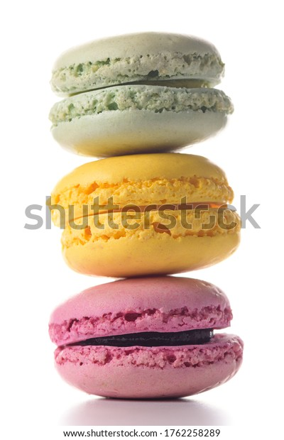 Three macaroons standing on top of each other on white background.