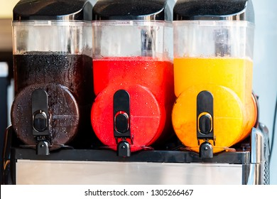 Three machines closeup of slush slushie cold drinks with slushy ice and colorful colors for refreshing summer with black, red and yellow