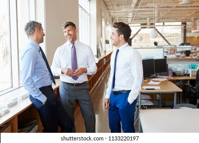 Three male corporate business colleagues chatting at work