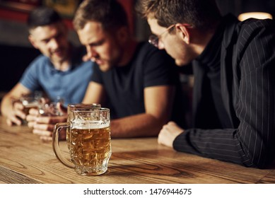 Three male friends in the bar. Supporting sad friend. Unity of people. With beer on the table.