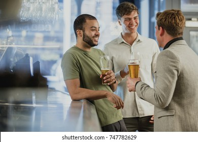 Three male friends are enjoying themselves at the bar after work, drinking pints of lager.