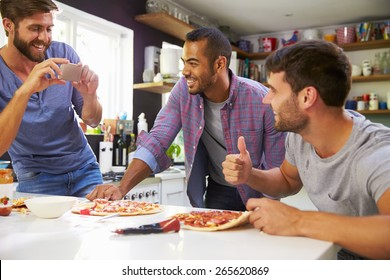 Three Male Friends Making Pizza In Kitchen Together