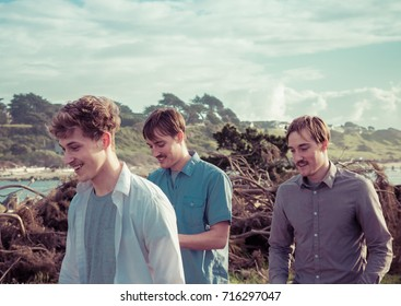 Three male friends walking outside; not posed, natural, landscape, nature