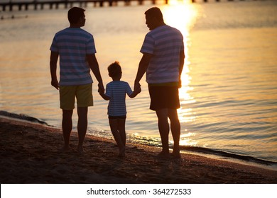 Three male generations by the sea at sunset