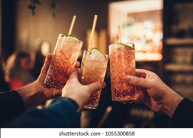 Three male hands holding three cocktail glasses againt blurred background in a cocktail bar