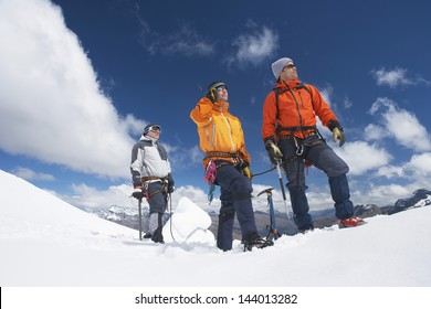 Three male mountain climbers reaching snowy peak against clouds
