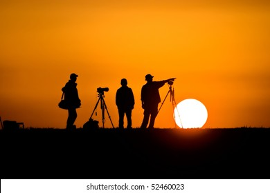 Three male photographers silhouetted against the setting sun.