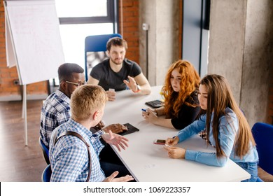 three male and two female students are talking about broblems in studing in the small room at the university