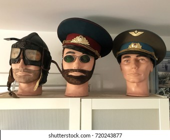 Three mannequin heads dressed as a World War One aviator and two Russian Officers from the Communist era.  The hammer and sickle emblem is a Communist symbol from the Russian Revolution, not a logo.
