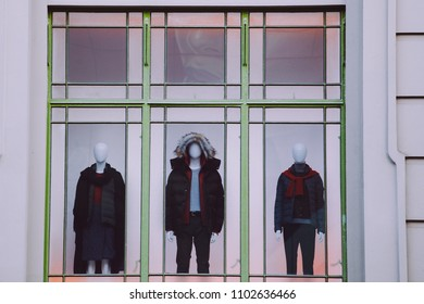 Three mannequins with clothes in storefront window closeup