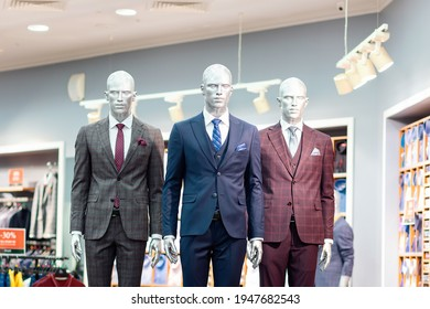 Three mannequins dressed in classic costumes, in a shop window. Shopping and consumerism.