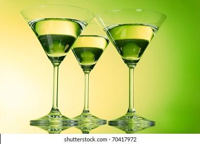 Three martini glasses on green background
