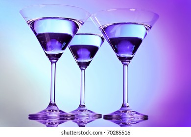 Three martini glasses on purple background