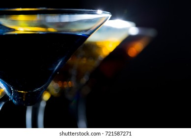 Three Martini Glasses in a row with a dark background with copy space.