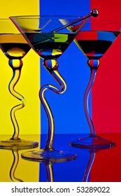 Three martinis in glasses with curved stems in front of colorful lighted background