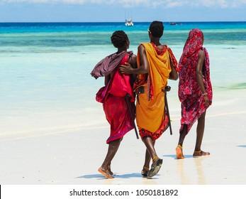 Three Masai boys walking in Nungwi Beach. Zanzibar, Tanzania, February 2018.