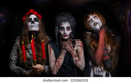 three masked girls made up for halloween horror and photomanipulation