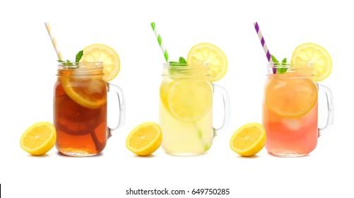 Three mason jar glasses of summer iced tea, lemonade, and pink lemonade drinks isolated on a white background