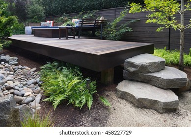 Three massive rocks form steps to a contemporary deck with bench inspired by oriental design.