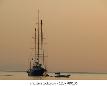 A three mast sailing yacht and a motor boat, at sunset in Glyfada, Greece