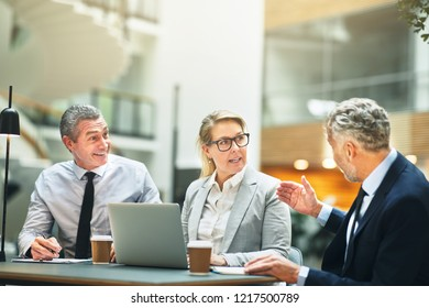 Three mature business colleagues discussing work together while having a meeting at a table in the lobby of a modern office building