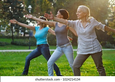 Three mature ladies doing yoga outdoors