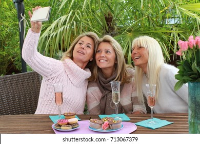 Three mature woman taking selfie on a terrace exterior shot