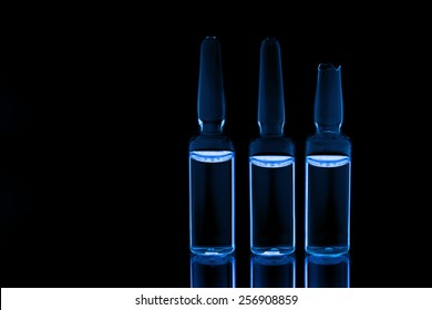 Three medical ampules on black background