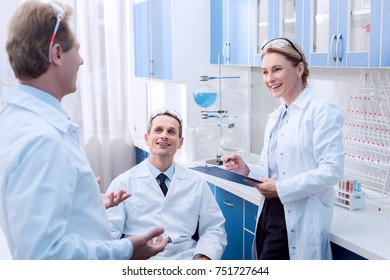 Three medical workers in lab coats smiling and talking in chemical laboratory