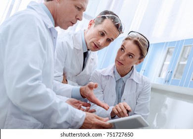 Three medical workers in white coats, discussing work while looking at digital tablet