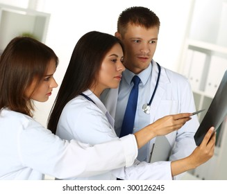 Three medicine doctors examining x-ray photography of patient to detect problem. Professional conversation, council of physicians. Working conference. Radiologist or traumatologist medical concept