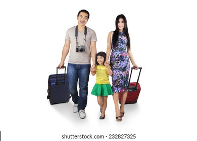 Three member of asian tourist walking in studio while carrying luggage