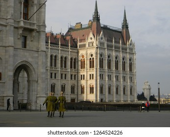 Three members of the Hungarian Honor Guard marching towards the Hungarian Parliament after the changing of the guard near the Hungarian flag on Kossuth Lajos ter, with tourists in the background