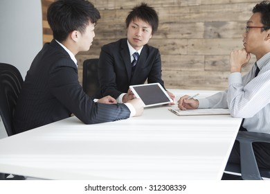 Three men to be meeting in a bright office