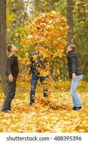 Three men in black jackets pop-up yellow maple leaves in park