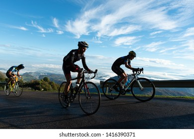 Three men cycling on the road in Angliru, Asturias 11 of October 2015