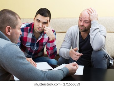 Three men discussing financial issues