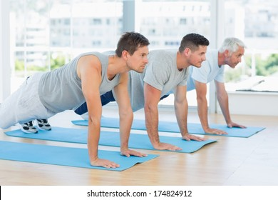 Three men doing push ups at fitness studio