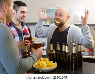 Three men drinking beer and laughing at house party