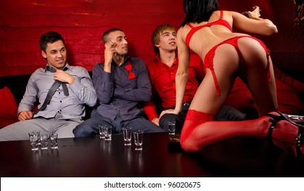 Three men drinking and looking at dancing woman.